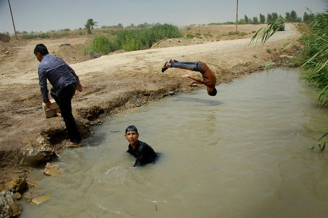 Iraqi_boys_swim_in_the_murky_waters_of_a_small_pond_near_Awad,_Iraq,_July_12,_2008_080712-A-ZF234-085